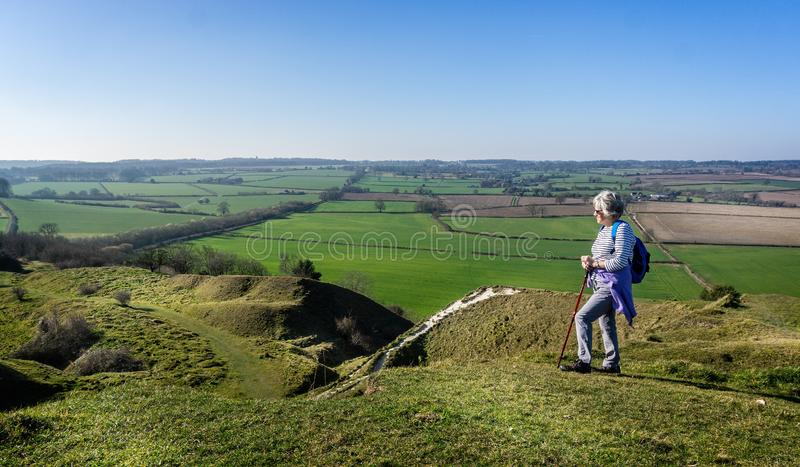 Mature female rambler admiring beautiful hilltop view from the top of White Sheet Hill in Wiltshire. UK stock photography