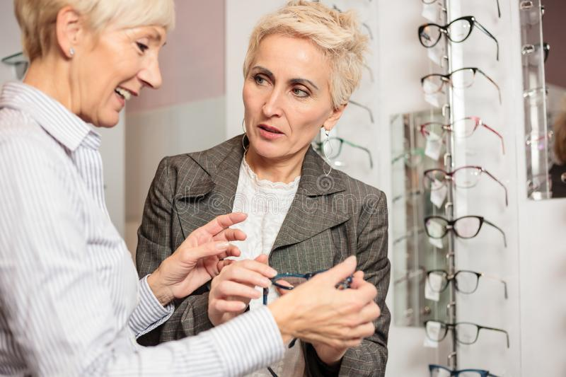 Mature female seller helping smiling senior woman to choose prescription glasses in optician store royalty free stock photography