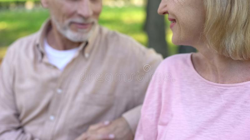Mature female smiling to handsome man, sitting on bench together, flirting stock photography