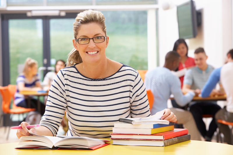 Mature Female Student Studying In Classroom With Books. And Smiling stock photos