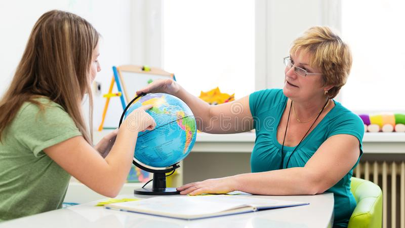 Mature female therapist working with a teenage girl with learning difficulties. Private geography tutoring session. royalty free stock images