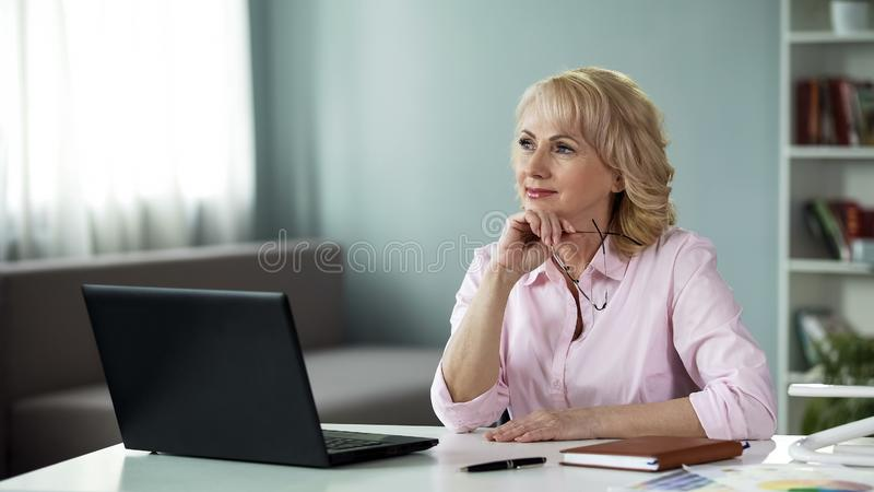 Mature female writer thinking of new series of adventure books in front laptop royalty free stock photo