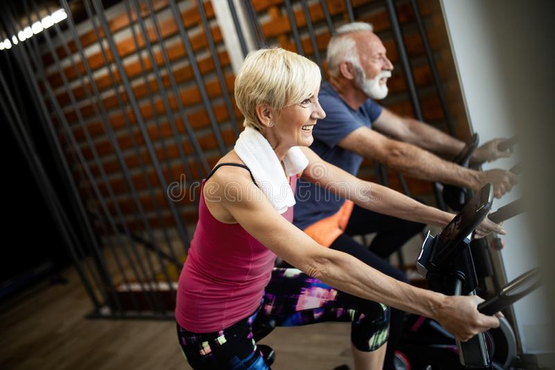 Mature fit couple exercising in gym to stay healthy. Senior fit couple exercising in gym to stay healthy royalty free stock image