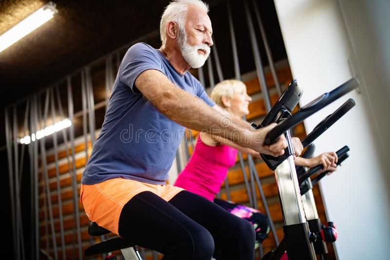 Mature fit people biking in the gym, exercising legs doing cardio workout cycling bikes. Fit senior people biking in the gym, exercising legs doing cardio royalty free stock images