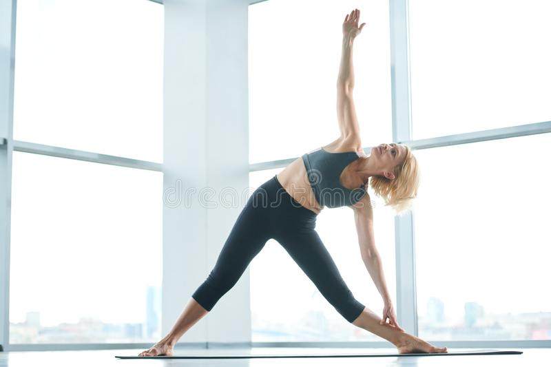 Woman side-bending. Mature flexible woman in activewear practicing exercise for stretching while raising one arm during side-bending on mat royalty free stock photography