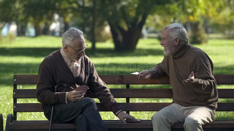 Mature friends playing cards having fun in park, active lifestyle, retirement royalty free stock photography