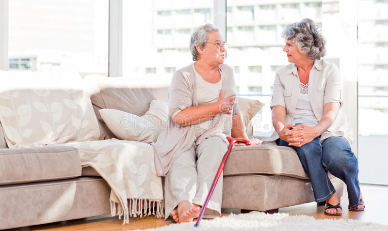 Mature friends talking on the sofa royalty free stock photos