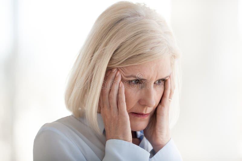 Mature frustrerad affärskvinna som lider från huvudvärkslut upp royaltyfri bild