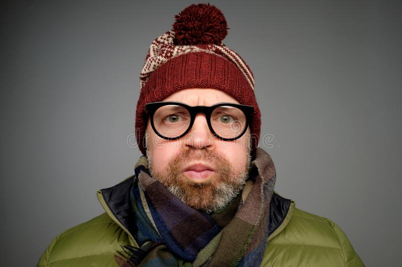 Mature funny man in warm clothes and glasses blowing his cheeks while being offended at somebody royalty free stock image