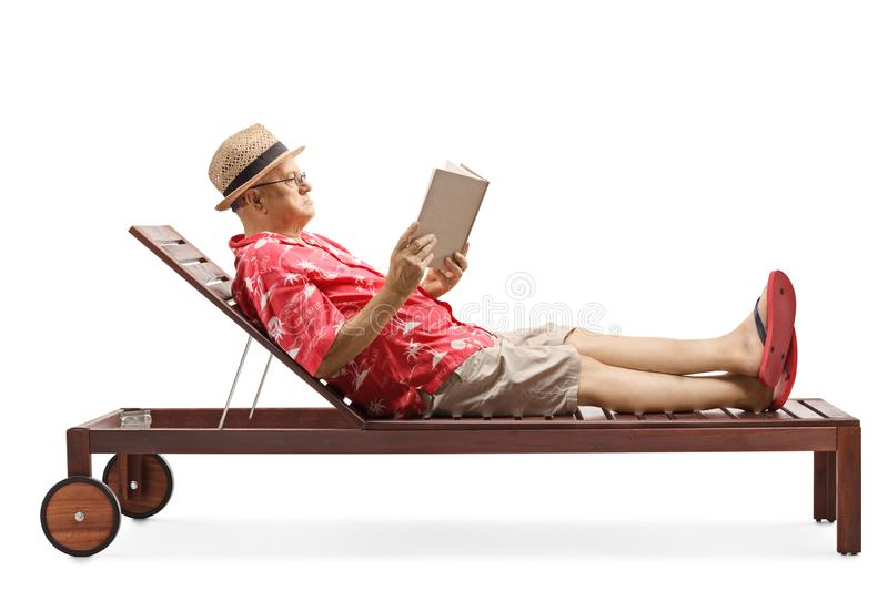 Mature gentleman enjoying on a lounge chair while reading a book stock photo