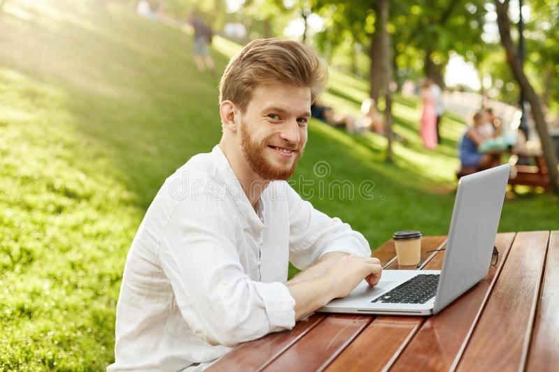 Mature ginger handsome man with beard in casual stylish clothes smiles, sitting in park, looking at camera posing with royalty free stock photos