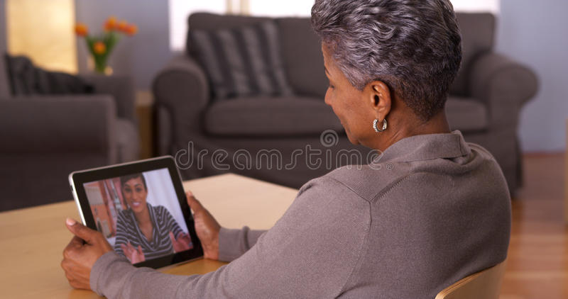 Mature grandmother talking with granddaughter on tablet. African grandmother woman talking with granddaughter on tablet stock photos