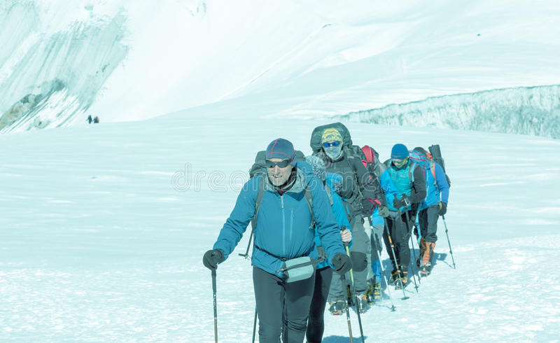 Mature Guide leading Group of Mountain Climbers on Glacier toned. Mature Guide in high altitude Boots and other Gear leading diverse Group of Mountain Climbers royalty free stock images