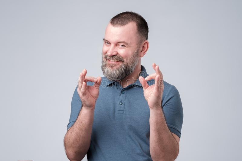 Mature guy in blue t-shirt showing ok or okay sign. stock images