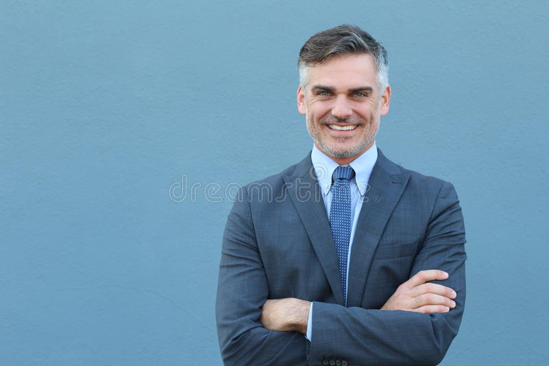 Mature handsome Caucasian businessman smiling with arms crossed stock image