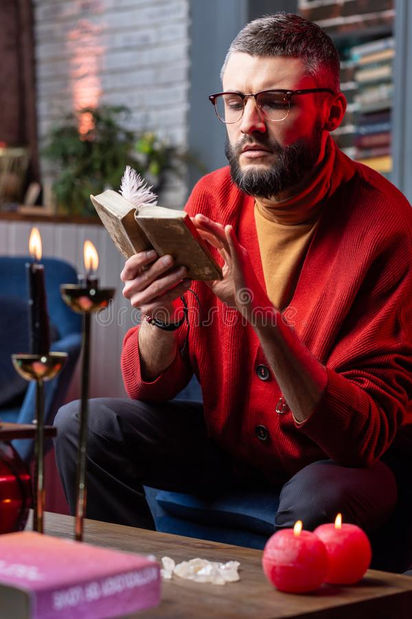 Mature handsome man having skills in future prediction reading old book royalty free stock photo