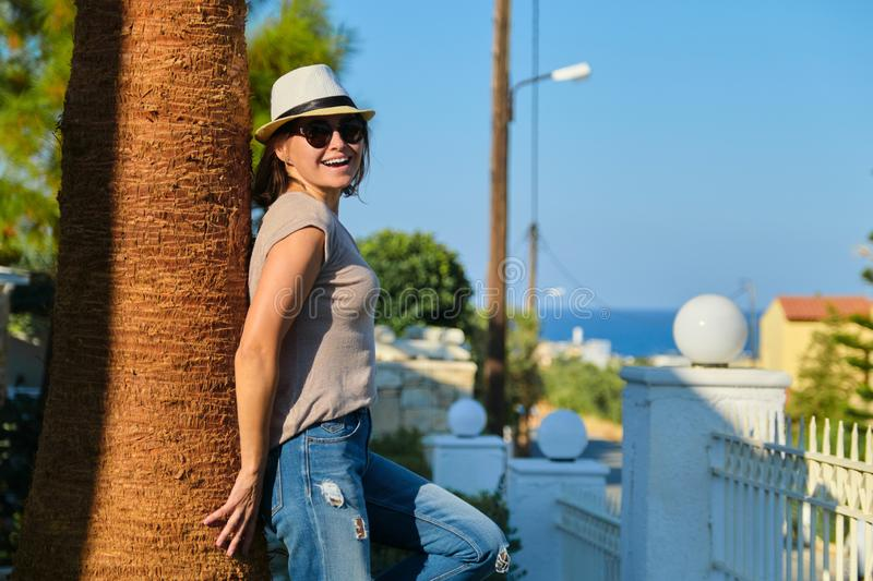 Mature happy beautiful woman in sunglasses hat standing near palm tree royalty free stock image