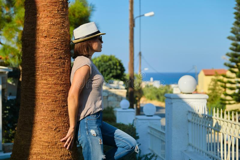 Mature happy beautiful woman in sunglasses hat standing near palm tree stock photos