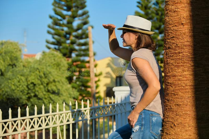 Mature happy beautiful woman in sunglasses hat standing near palm tree royalty free stock photo