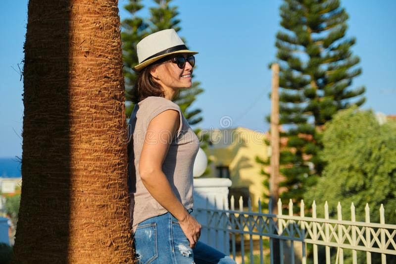 Mature happy beautiful woman in sunglasses hat standing near palm tree stock photo