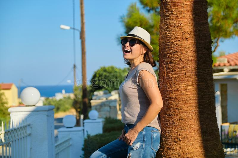 Mature happy beautiful woman in sunglasses hat standing near palm tree stock photography