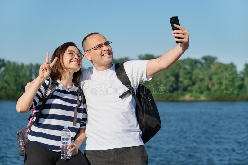 Mature happy couple taking selfie photo on phone, people relaxing near river in summer evening park royalty free stock images