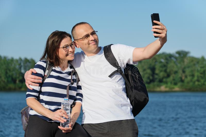 Mature happy couple taking selfie photo on phone, people relaxing near river in summer evening park stock images