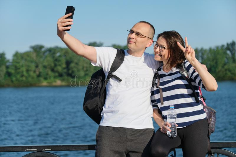 Mature happy couple taking selfie photo on phone, people relaxing near river in summer evening park stock photo