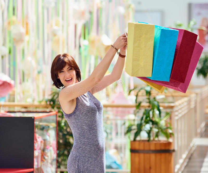 Mature Happy Woman With colored Shopping Bags royalty free stock photos