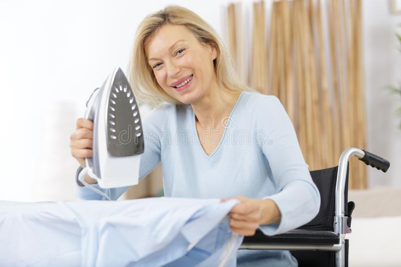 Mature happy woman irons clothes royalty free stock image