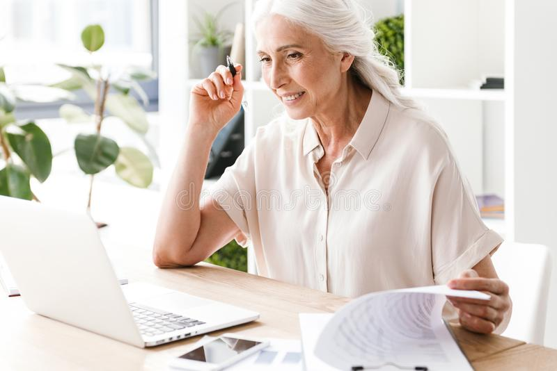 Mature happy woman writing notes. royalty free stock photos