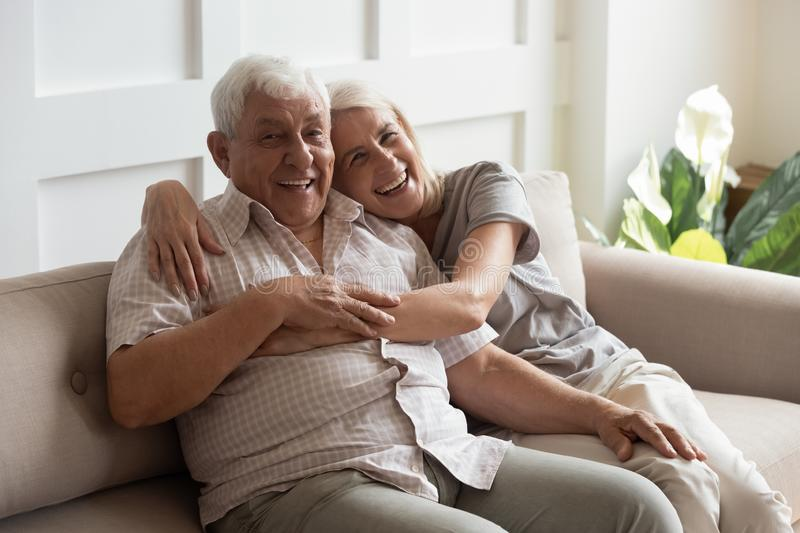 Happy mature couple resting on couch looking at camera. Mature healthy couple sitting on couch laughing looks at camera, 80s grey-haired husband 60s wife spend royalty free stock photo