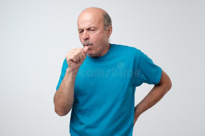 Mature hispanic man in blue t-shirt man coughing being ill. royalty free stock photography