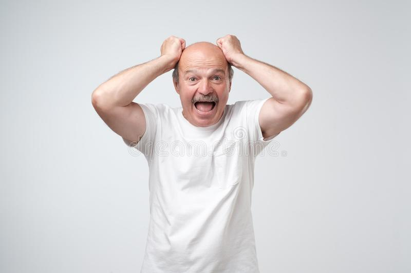Mature hispanic man feels shock and surprise with overly face expression. stock images