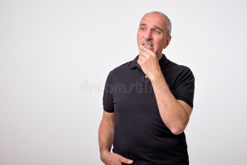 Mature hispanic man thinking with hands on chin looking away. Close up portrait of real people. Concept photo of puzzled, confused, worried and thoughtful man stock images