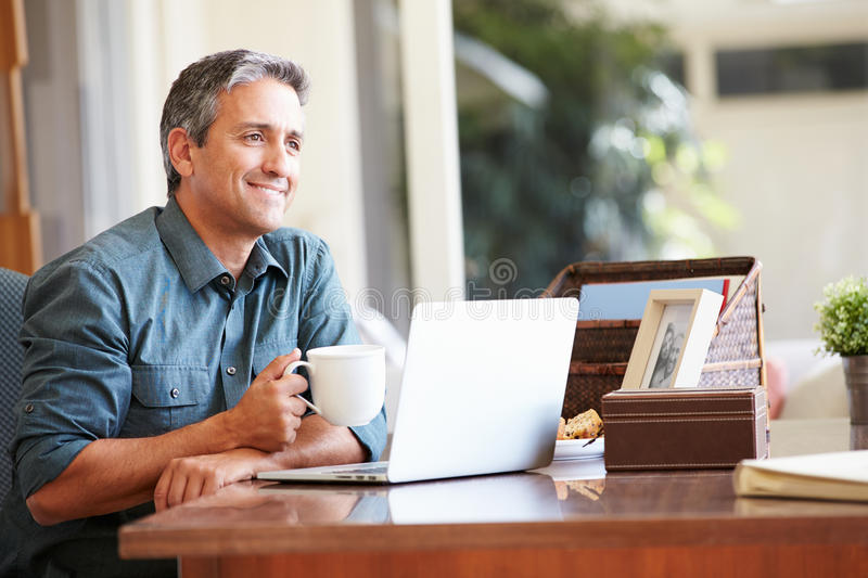 Mature Hispanic Man Using Laptop On Desk At Home. Holding Hot Drink Smiling stock images