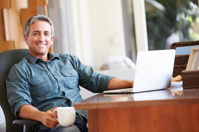 Mature Hispanic Man Using Laptop On Desk At Home. Holding Hot Drink Smiling At Camera royalty free stock images