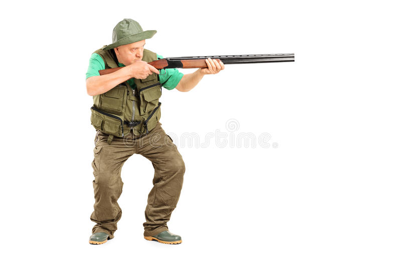 Mature hunter aiming at something with a gun stock photos