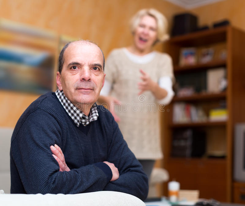 Mature husband tired of yelling wife. Mature spouses having a quarrel in a living room. Senior husband is tired of his wife yelling and sitting turned away from stock photo