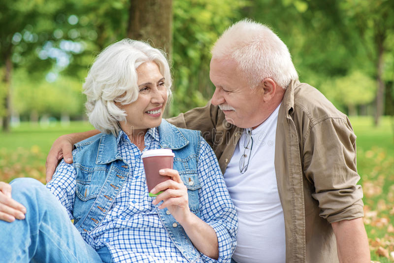 Mature husband and wife having rest in park stock photography