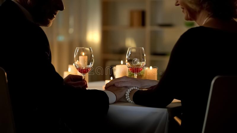 Mature husband and wife holding hands in restaurant, aged couple togetherness royalty free stock photo
