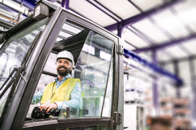 Mature industrial man engineer sitting in a forklift in a factory. stock photo