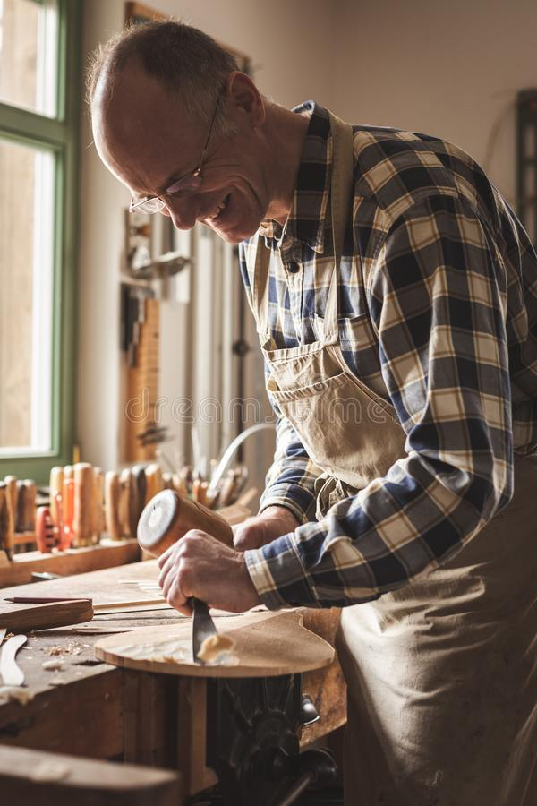 Craftsman working with chisel and mallet. Mature instrument maker is working with a mallet and a chisel inside his traditional workshop. He is smiling and royalty free stock image