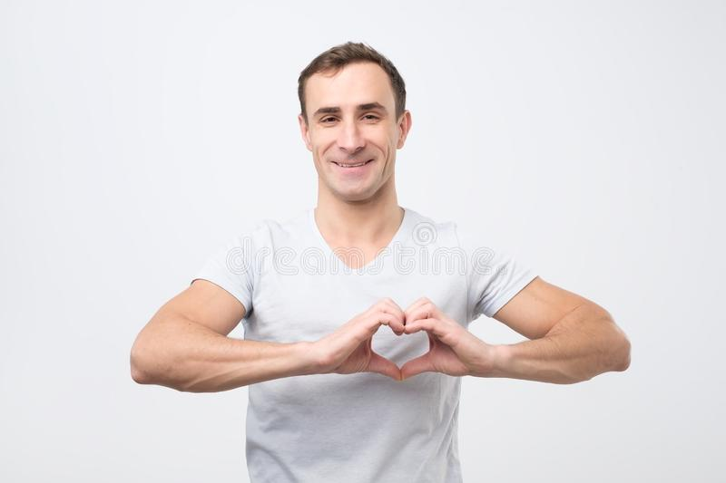 Mature italian man making out of hands heart. Doing charity work stock photos