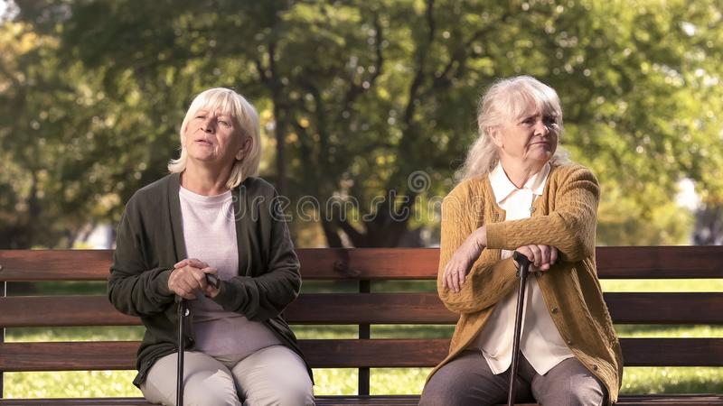 Mature ladies sitting separately on bench in park, friends argued and quarreled stock photography