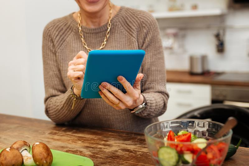 Mature lady in beige warm sweater carrying blue tablet stock image