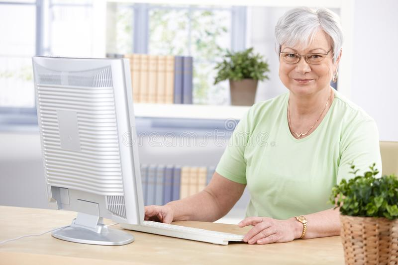 Mature lady with computer smiling. Mature lady browsing internet at home, smiling stock photography
