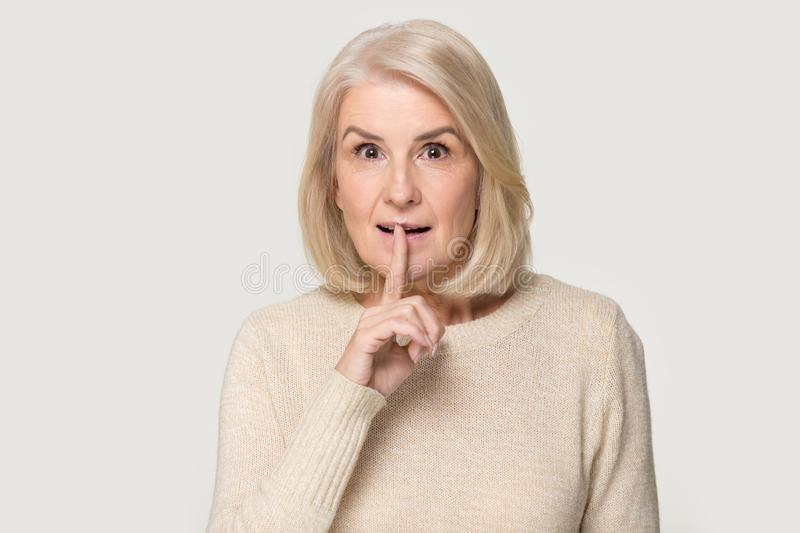 Mature lady keep finger on lips ask silence royalty free stock images