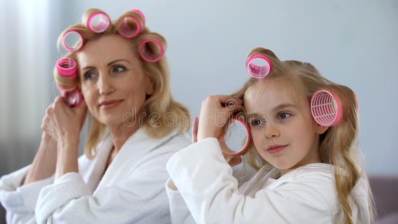 Mature lady and little girl rolling hair together morning, beauty and hairstyle royalty free stock photography