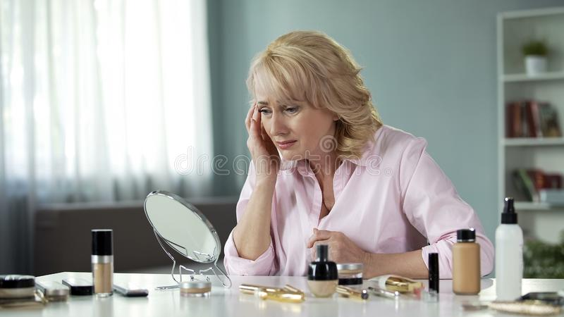Mature lady looking with disgust at her sagging skin and wrinkles, aging process. Stock photo stock image